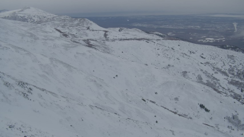 4K aerial video fly over snowy mountain slopes reveal Anchorage, Chugach Mountains, Alaska Aerial Stock Footage | AK0001_1507