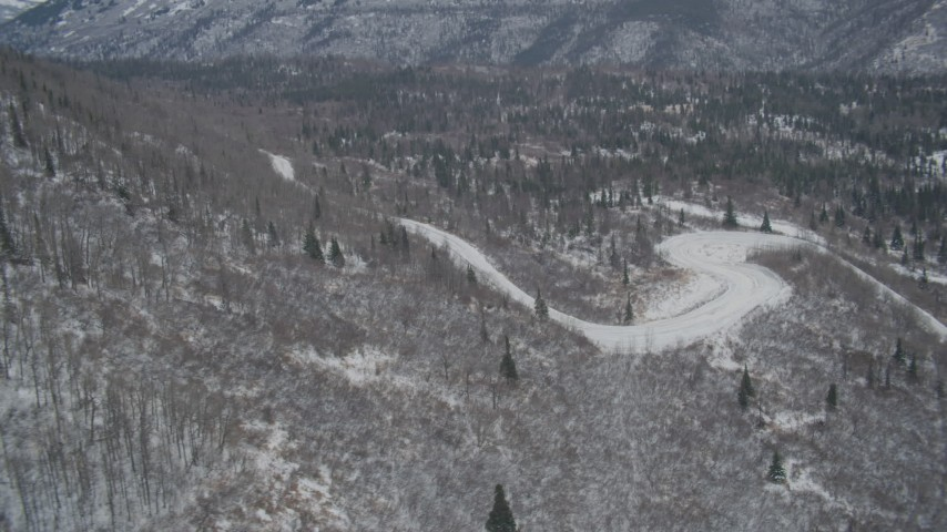 4K stock footage aerial video road through snowy, wooded foothills, Chugach Mountains, Alaska Aerial Stock Footage | AK0001_1512