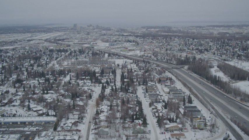 4K stock footage aerial video following Glenn Highway, revealing Downtown Anchorage, Alaska in snow Aerial Stock Footage | AK0001_1516