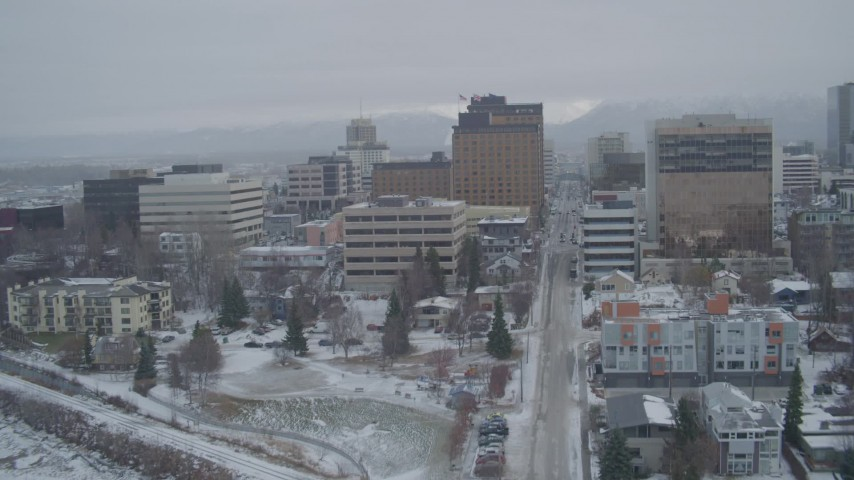 4K stock footage aerial video flying over Cook Inlet into snowy Downtown Anchorage, West 5th Avenue, Alaska Aerial Stock Footage | AK0001_1524