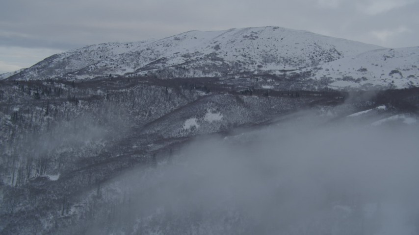 4K stock footage aerial video flying through fog over snowy, wooded slopes in Chugach Mountains, Alaska Aerial Stock Footage | AK0001_1538