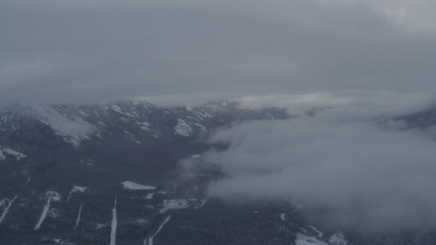 4K aerial video flying between clouds near Chugach Mountains, Alaska in snow Aerial Stock Footage | AK0001_1552