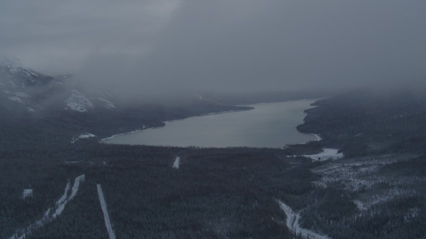 4K stock footage aerial video descending through clouds revealing Eklutna Lake, Alaska in snow Aerial Stock Footage | AK0001_1554