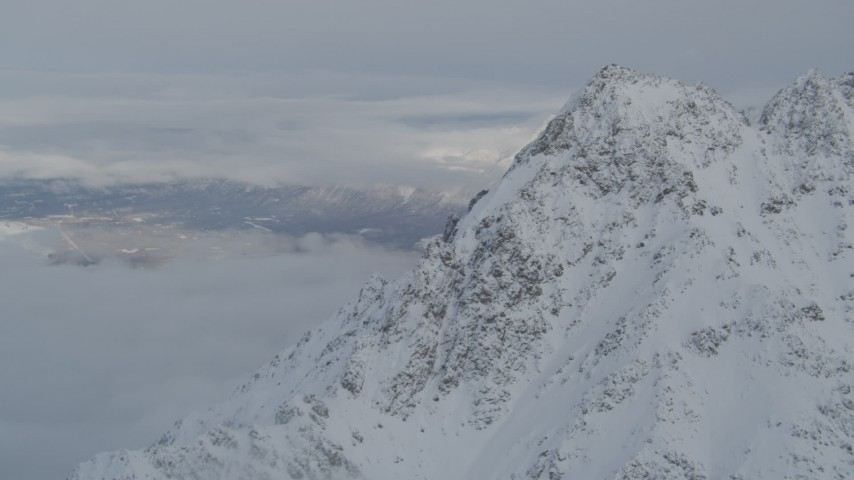 4K stock footage aerial video low clouds covering Butte, snowy mountain peak, Chugach Mountains, Alaska Aerial Stock Footage | AK0001_1564