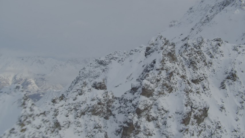 4K stock footage aerial video flying by snow covered rocky mountain ridges, Chugach Mountains, Alaska Aerial Stock Footage | AK0001_1565