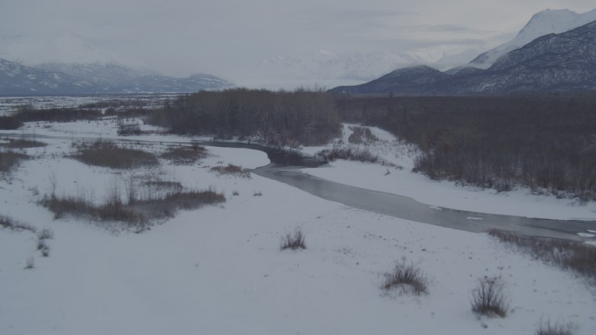 4K stock footage aerial video flying over river, snow covered path through woods, Knik River Valley, Alaska Aerial Stock Footage | AK0001_1592