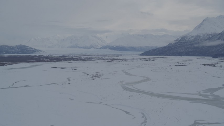 4K aerial video Knik Glacier, Chugach Mountains seen from snowy Knik River Valley, Alaska Aerial Stock Footage | AK0001_1597