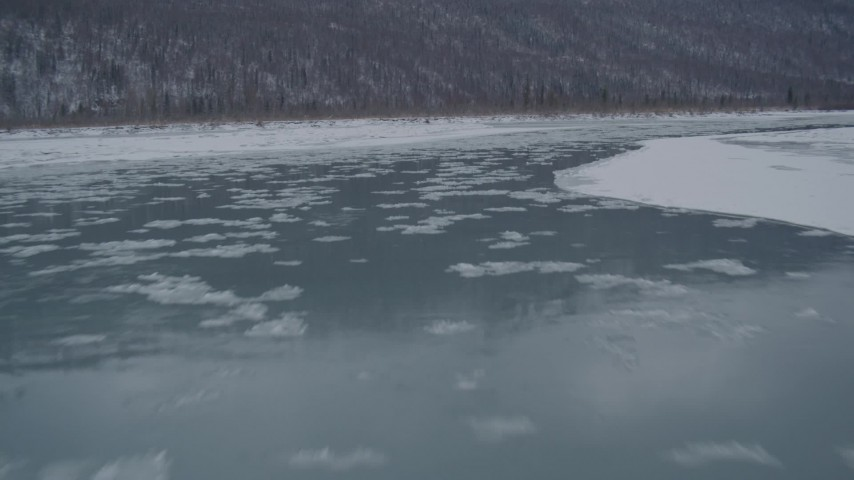 4K stock footage aerial video flying low over icy river toward snow covered shore, Knik River Valley, Alaska Aerial Stock Footage | AK0001_1610