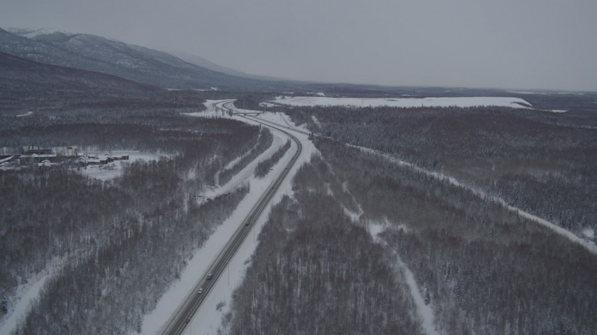4K aerial video snowy Glenn Highway stretching toward Chugach Mountains, Eagle River, Alaska Aerial Stock Footage | AK0001_1636