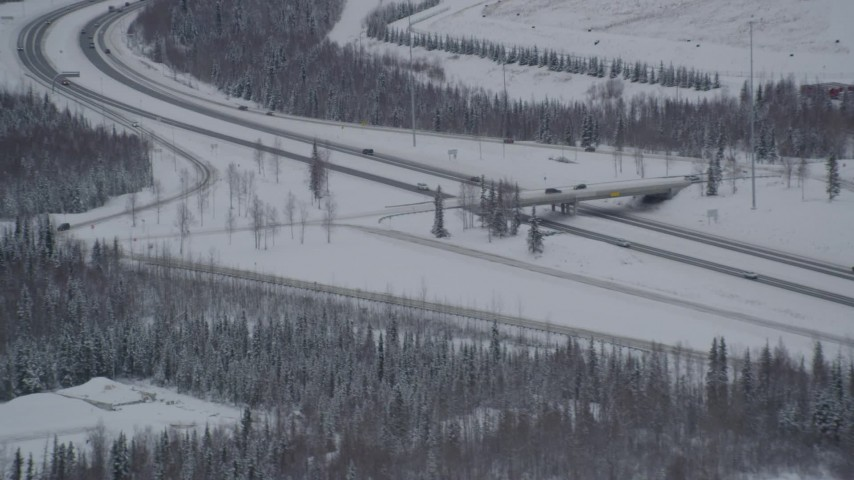 4K aerial video flying by Eagle River Loop Road overpass over Glenn Highway, Alaska in snow Aerial Stock Footage | AK0001_1637
