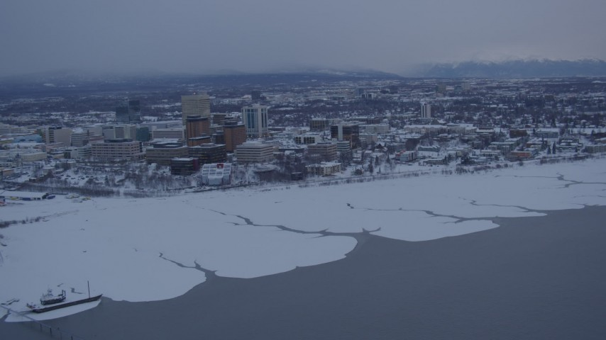 4K stock footage aerial video flying away from snowy Downtown Anchorage over Cook Inlet at twilight, Alaska Aerial Stock Footage | AK0001_1655