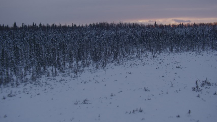 4K stock footage aerial video flying low over frozen, snowy ground at sunset, Point MacKenzie, Alaska Aerial Stock Footage | AK0001_1672