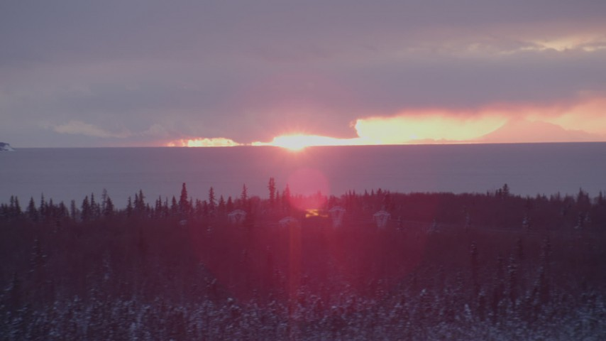 4K stock footage aerial video the sun setting behind clouds, Point MacKenzie, Alaska in snow Aerial Stock Footage | AK0001_1675