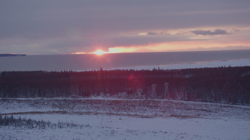 4K stock footage aerial video the sunset behind clouds seen from snow covered Point MacKenzie, Alaska Aerial Stock Footage | AK0001_1676