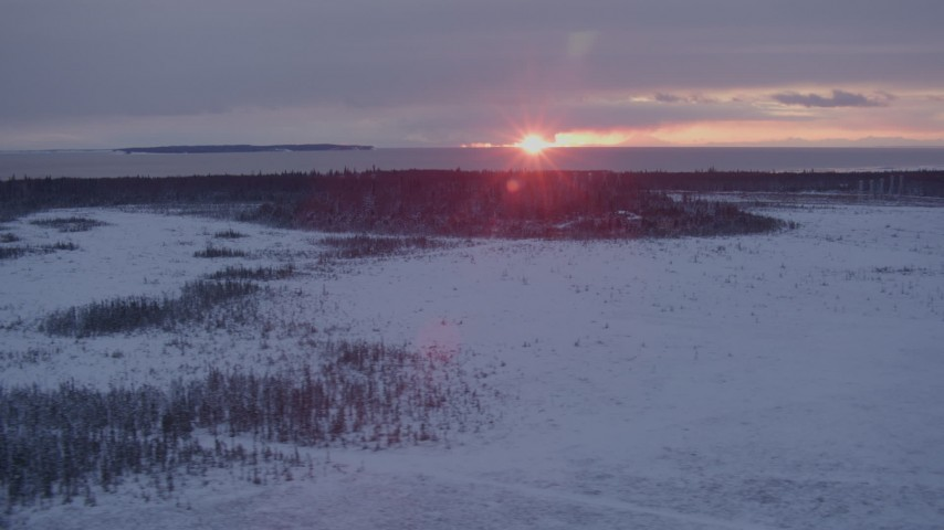4K stock footage aerial video the setting sun behind clouds seen from snow covered Point MacKenzie, Alaska Aerial Stock Footage | AK0001_1678
