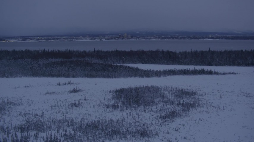 4K stock footage aerial video Downtown Anchorage across the inlet, seen from snowy Point MacKenzie at twilight, Alaska Aerial Stock Footage | AK0001_1686