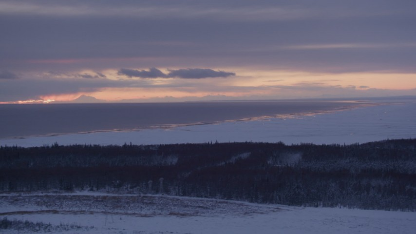 4K stock footage aerial video twilight lit clouds over Cook Inlet seen from snow covered Point MacKenzie, Alaska Aerial Stock Footage | AK0001_1690