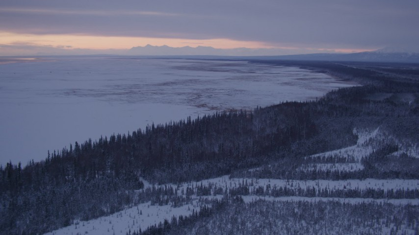 4K stock footage aerial video following snowy, wooded shore of Point MacKenzie at twilight, Alaska Aerial Stock Footage | AK0001_1692