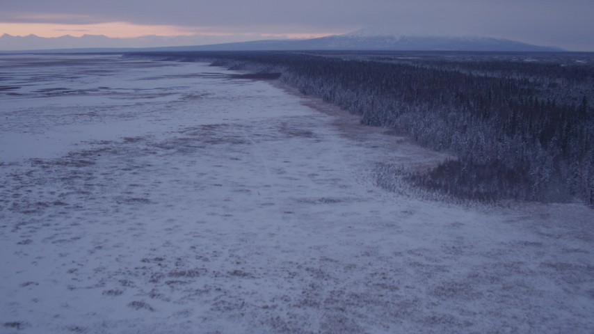 4K stock footage aerial video flying over frozen, snow covered ground at twilight, Point MacKenzie, Alaska Aerial Stock Footage | AK0001_1693