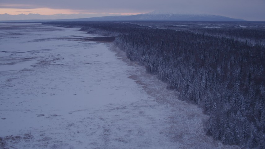 4K stock footage aerial video flying over frozen, snowy ground beside forest at twilight, Point MacKenzie, Alaska Aerial Stock Footage | AK0001_1694