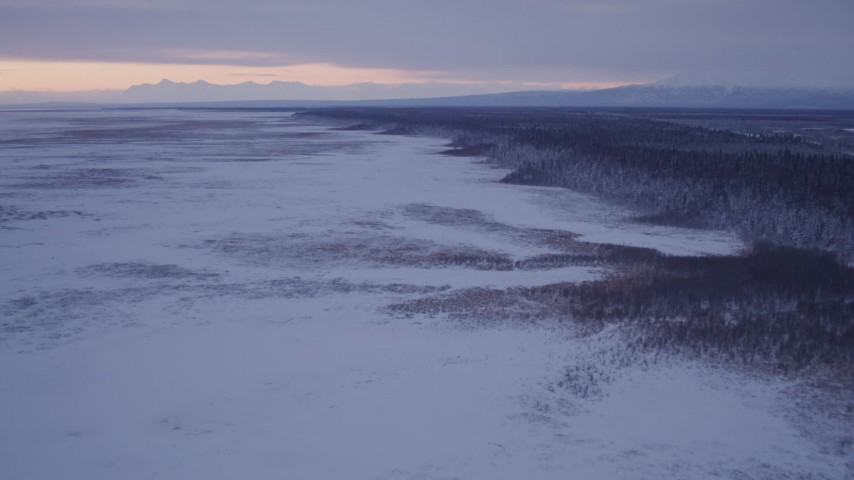 4K stock footage aerial video flying over frozen, snow covered ground at twilight, Point MacKenzie, Alaska Aerial Stock Footage | AK0001_1695