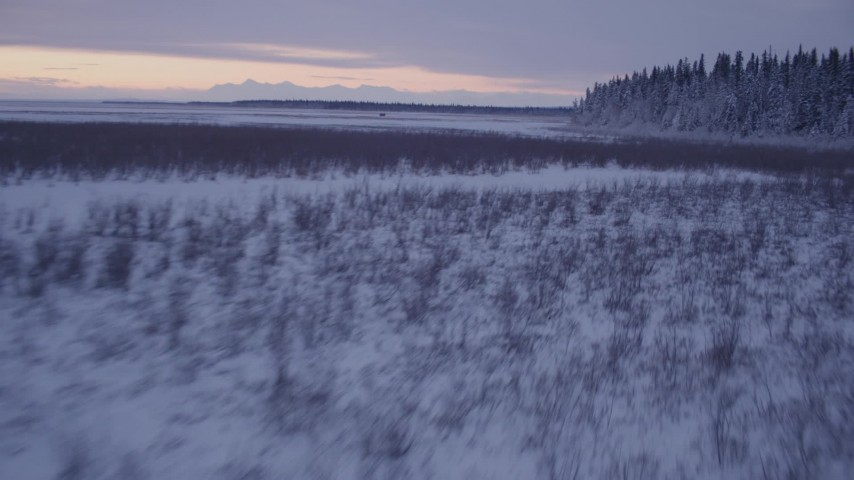 4K stock footage aerial video flying low over frozen, snow covered ground at twilight, Point MacKenzie, Alaska Aerial Stock Footage | AK0001_1697
