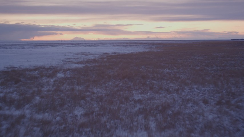 4K stock footage aerial video flying low over frozen, snowy ground and grass at twilight, Point MacKenzie, Alaska Aerial Stock Footage | AK0001_1701