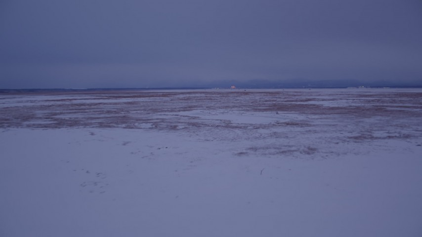 4K stock footage aerial video flying low over frozen, snow covered ground at twilight, Point MacKenzie, Alaska Aerial Stock Footage   AK0001_1710