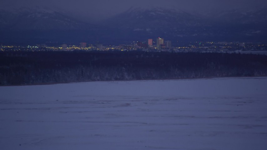 4K stock footage aerial video tilt up from snowy ground revealing Downtown Anchorage skyline, Alaska, night Aerial Stock Footage | AK0001_1714