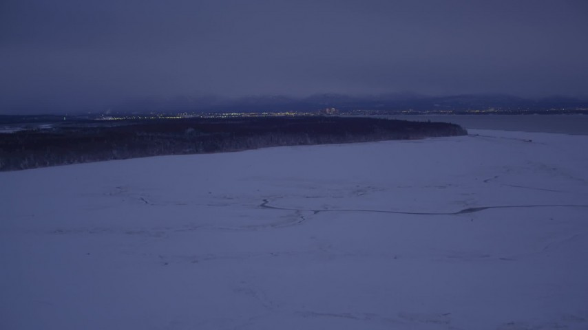 4K stock footage aerial video flying over snow covered ground toward forest at night, Point MacKenzie, Alaska Aerial Stock Footage | AK0001_1715