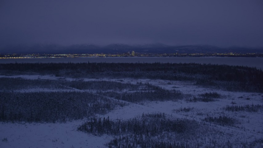 4K stock footage aerial video Downtown Anchorage skyline, snowy ground, Point MacKenzie, Alaska, night Aerial Stock Footage | AK0001_1717