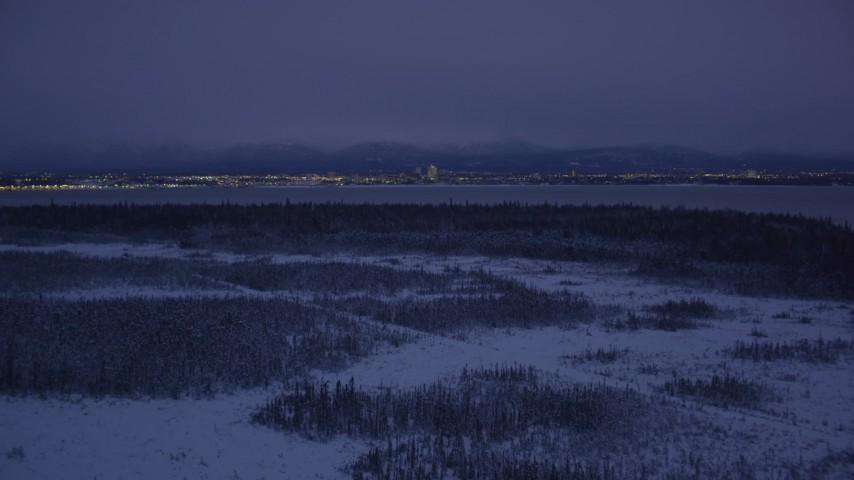 4K stock footage aerial video Downtown Anchorage skyline, snowy ground, Point MacKenzie, Alaska, night Aerial Stock Footage | AK0001_1717