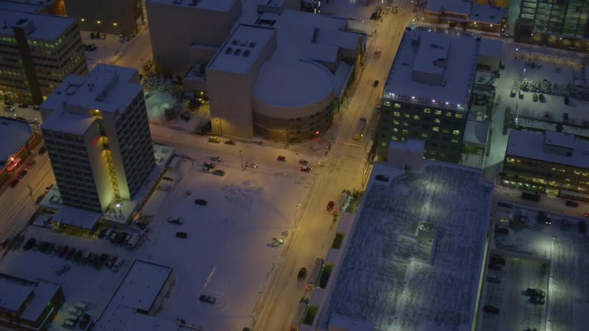 4K aerial video following West 6th Avenue in snow covered Downtown Anchorage at night, Alaska Aerial Stock Footage | AK0001_1724