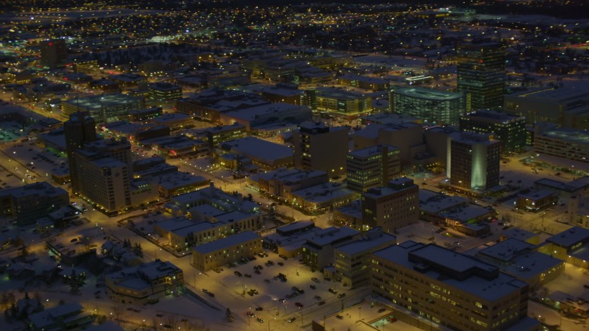 4K stock footage aerial video orbit office buildings and streets in snow covered Downtown Anchorage at night, Alaska Aerial Stock Footage | AK0001_1729