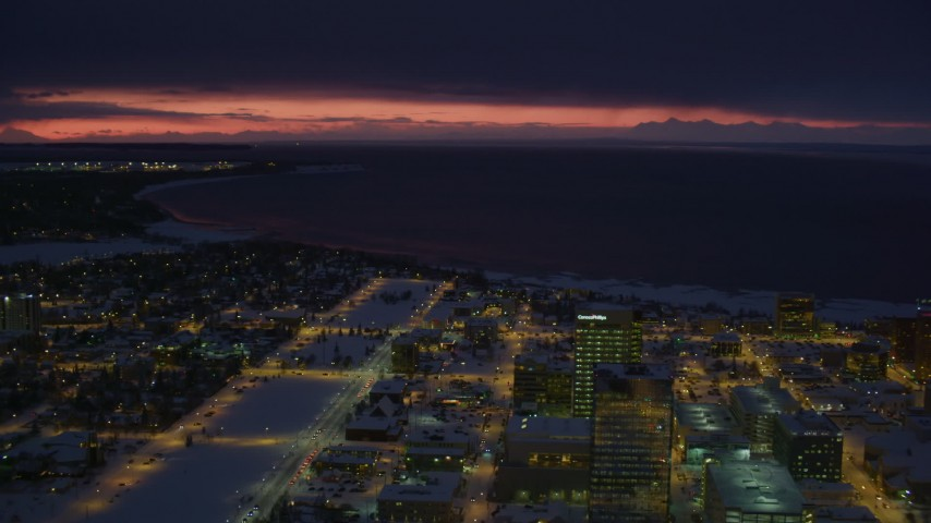 4K stock footage aerial video sunset lit horizon seen from snow covered Downtown Anchorage at night, Alaska Aerial Stock Footage | AK0001_1731