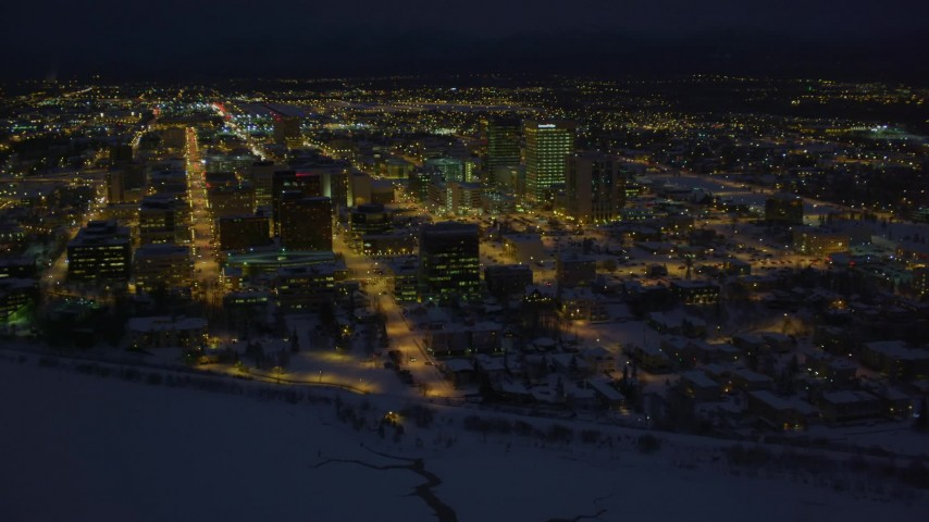 4K stock footage aerial video snowy Downtown Anchorage buildings near the shore of Cook Inlet, Alaska, night Aerial Stock Footage | AK0001_1734