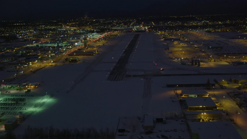 4K stock footage aerial video flying toward snow covered Merrill Field at night, Anchorage, Alaska Aerial Stock Footage | AK0001_1736
