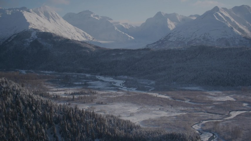 4K stock footage aerial video wooded slopes and river valley, tilt up to snow capped Chugach Mountains, Alaska Aerial Stock Footage   AK0001_1766