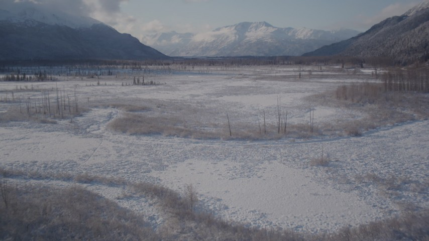 4K stock footage aerial video flying over river and frozen, snowy ground toward Chugach Mountains, Alaska Aerial Stock Footage | AK0001_1771