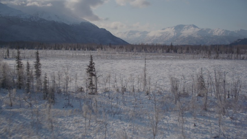 4K stock footage aerial video flying low over frozen, snowy ground toward Chugach Mountains, Alaska Aerial Stock Footage | AK0001_1773