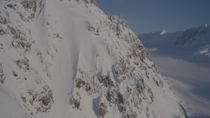 4K aerial video rounding snow covered slopes in Chugach Mountains, Alaska Aerial Stock Footage | AK0001_1777
