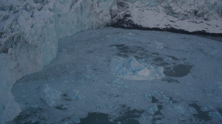 4K stock footage aerial video pan from edge of snow covered glacier, to Harriman Fjord, revealing chunk of glacial ice, Alaska Aerial Stock Footage | AK0001_1817