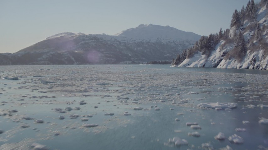 4K stock footage aerial video flying low over surface of Harriman Fjord bordered by snowy mountains, Alaska Aerial Stock Footage | AK0001_1829