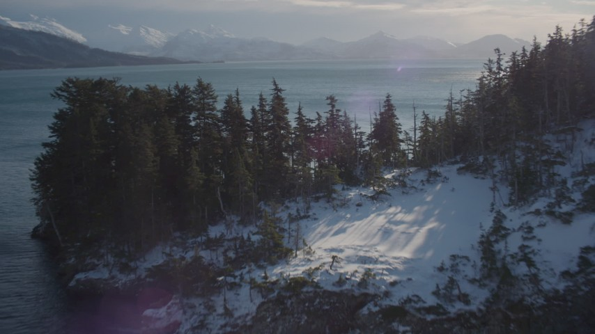4K stock footage aerial video flying over snowy, wooded shore to sun reflected water in Port Wells, Alaska Aerial Stock Footage | AK0001_1836