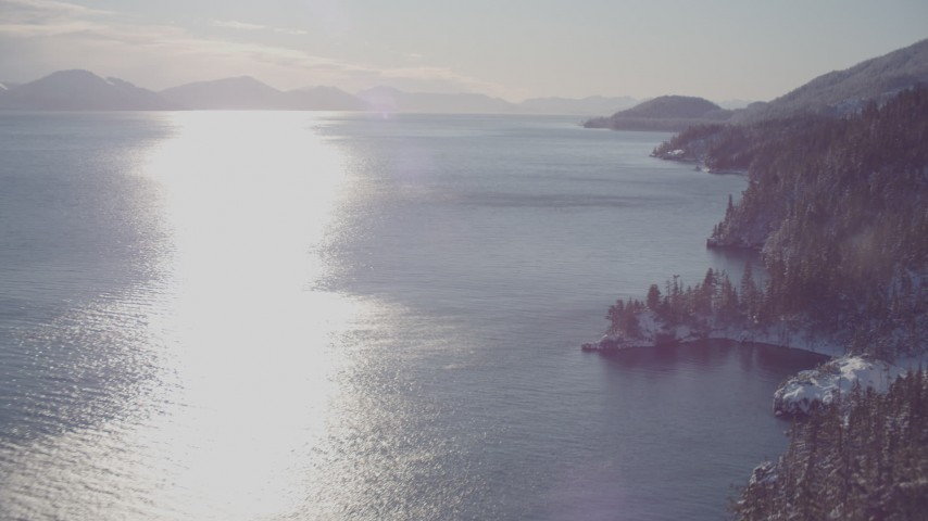 4K stock footage aerial video he sun reflecting off of water in Port Wells next to snowy, wooded shore, Alaska Aerial Stock Footage | AK0001_1838