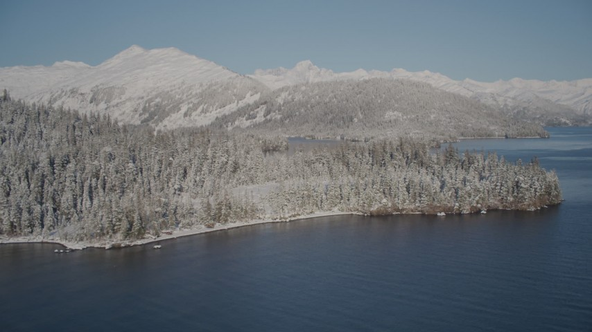 4K stock footage aerial video descending toward Port Wells and the snowy, wooded shore, Alaska Aerial Stock Footage | AK0001_1879