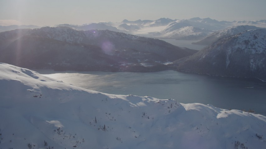 4K stock footage aerial video flying over snow covered mountain toward Pigot Bay, Alaska Aerial Stock Footage | AK0001_1895