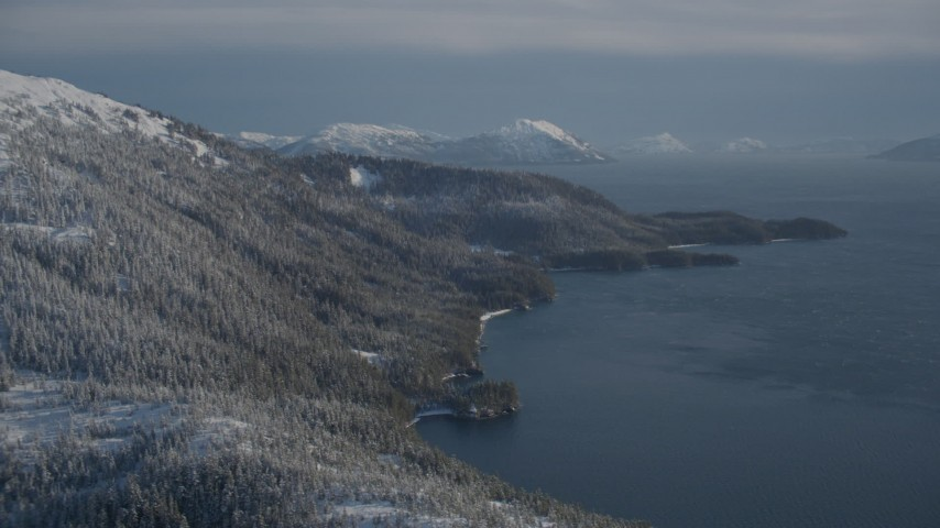 4K stock footage aerial video snowy wooded slopes along shore of Pigot Bay, mountains, Port Wells, Alaska Aerial Stock Footage | AK0001_1896