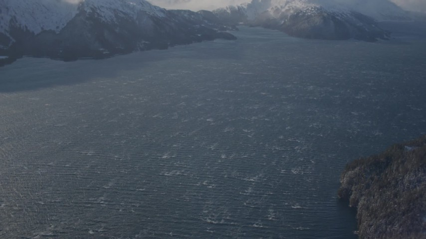 4K stock footage aerial video windblown water of Passage Canal beside snowy shore, Alaska, tilt to Chugach Mountains Aerial Stock Footage | AK0001_1905