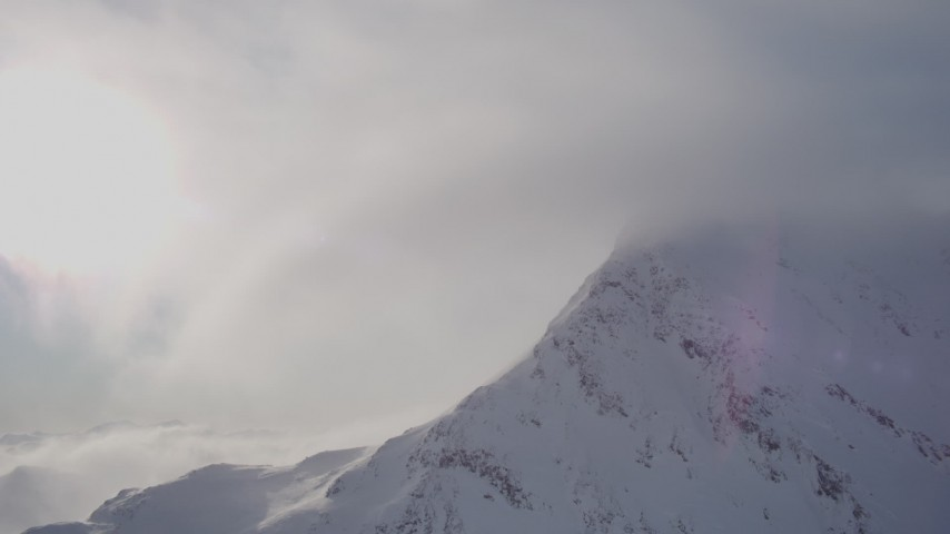 4K stock footage aerial video flying by cloud, snow covered mountains summit, Chugach Mountains, Alaska Aerial Stock Footage | AK0001_1915